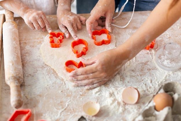 Handen die deeg met koekjevormen snijden