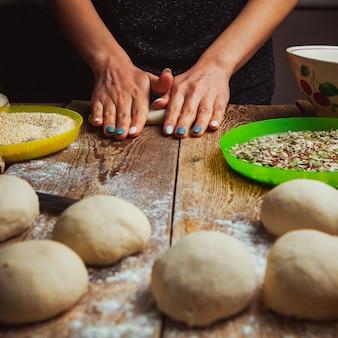 Handen die deeg vormen om turks ongezuurd broodje simit zijaanzicht voor te bereiden.