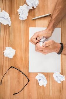 Handen die document op houten bureau verfrommelen