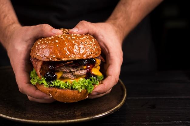 Handen die dubbele hamburger met kaas houden