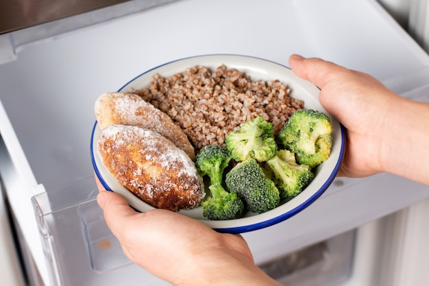 Handen die een bord met diepvriesproducten uit de vriezer van de koelkast halen