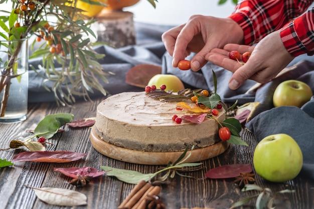 Handen die een bruine moussecake met bessen versieren