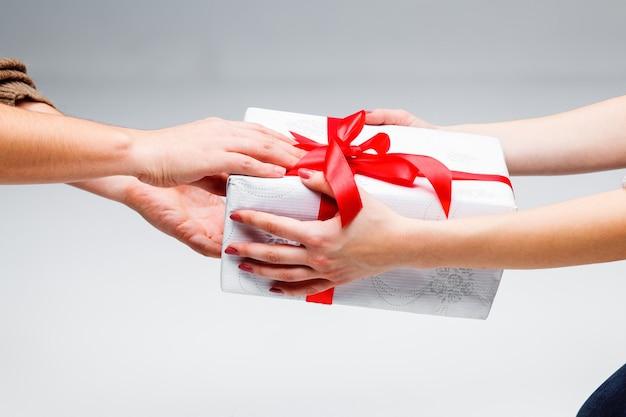 Handen die een cadeau geven en ontvangen