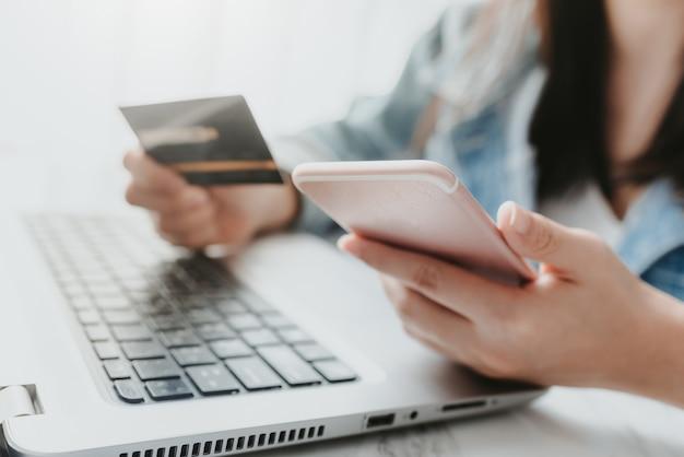 Handen die een creditcard houden en slimme telefoon voor online het winkelen gebruiken