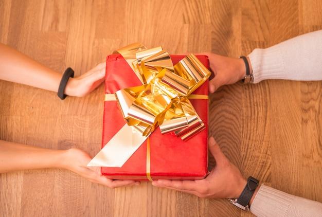 Handen die een doos van de kerstmisgift geven en ontvangen