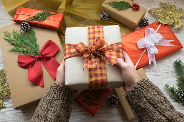 Handen die een doos van de kerstmisgift houden