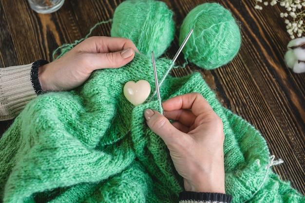 Handen die een gezellige groene trui breien