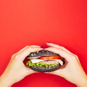 Handen die een hamburger met sla houden
