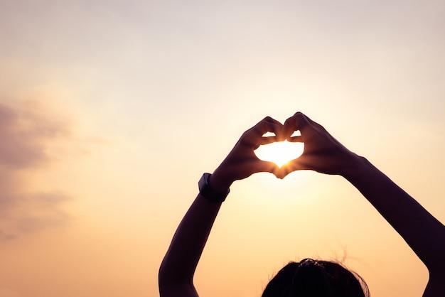 Handen die een hartvorm met zonsondergangsilhouet vormen