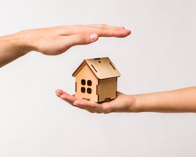Handen die een houten plattelandshuisje beschermen