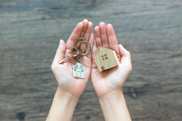 Handen die een klein huis en sleutels houden