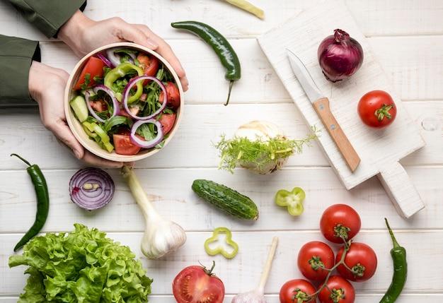 Handen die een kom met salade schikken