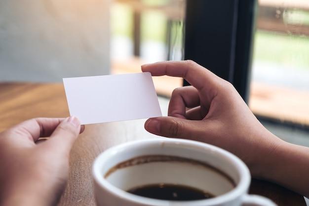 Handen die een leeg adreskaartje met koffiekop op lijst houden