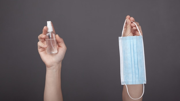 Handen die een medisch blauw gezichtsmasker en een fles antisepticum voor handen op een donkere achtergrond houden. quarantainebeschermende maatregel tegen het virus covid-19, pandemie