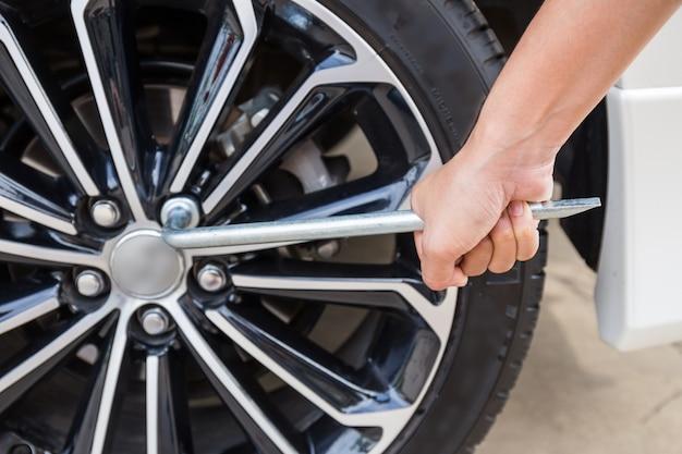 Handen die een modern autowiel (stalen velg) demonteren met een steeksleutel voor wisselwiel