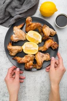 Handen die een plaat met heerlijke keukenvleugels houden