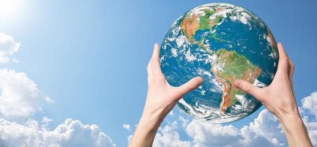 Handen die een planeet, aarde op een achtergrond van aard blauwe hemel met mooie witte wolken en zonlicht houden. het concept van de duurzame aarde. elementen van deze afbeelding geleverd door nasa.