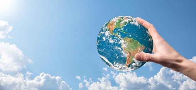 Handen die een planeet, aarde op een achtergrond van aard blauwe hemel met mooie witte wolken en zonlicht houden. het concept van de duurzame aarde. elementen van deze afbeelding ingericht
