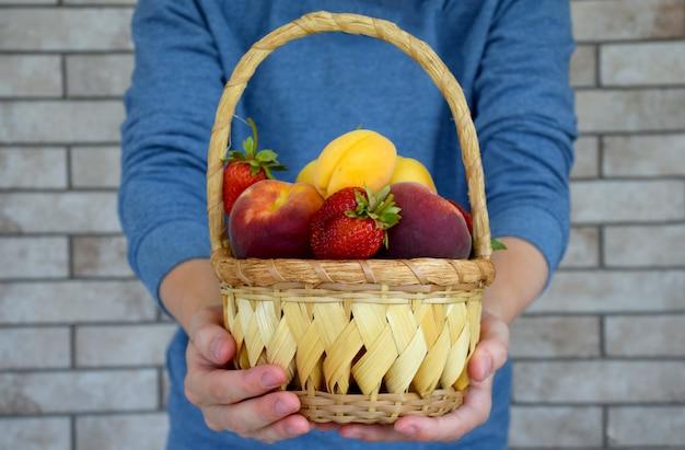 Handen die een rieten mandhoogtepunt van rijpe organische vruchten op bakstenen muurachtergrond houden