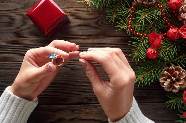 Handen die een ring met een blauwe steen