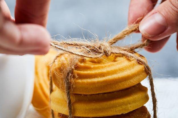 Handen die een stapel koekjes binden.