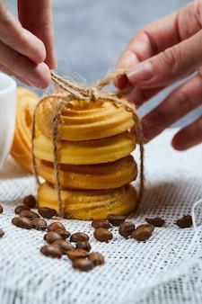 Handen die een stapel koekjes met koffiebonen binden.