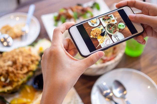 Handen die een telefoon gebruiken om foto's van voedsel te nemen
