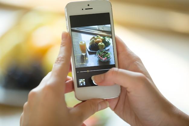 Handen die een telefoon met voedselfoto op het scherm houden