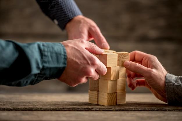 Handen die een toren van houtsneden bouwen