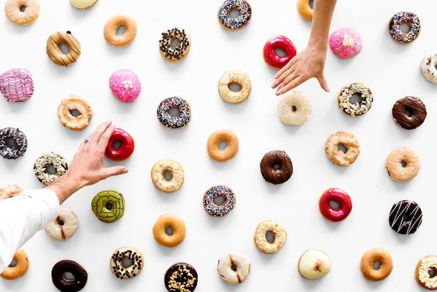 Handen die een verscheidenheid van doughnutaroma selecteren