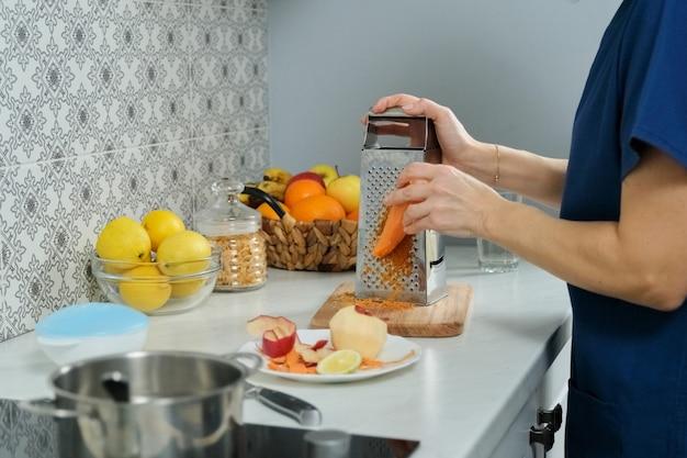 Handen die een wortel in de keuken raspen