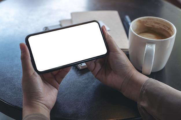 Handen die een zwarte mobiele telefoon met een leeg scherm horizontaal vasthouden en gebruiken om te kijken met een koffiekopje en notebooks op tafel