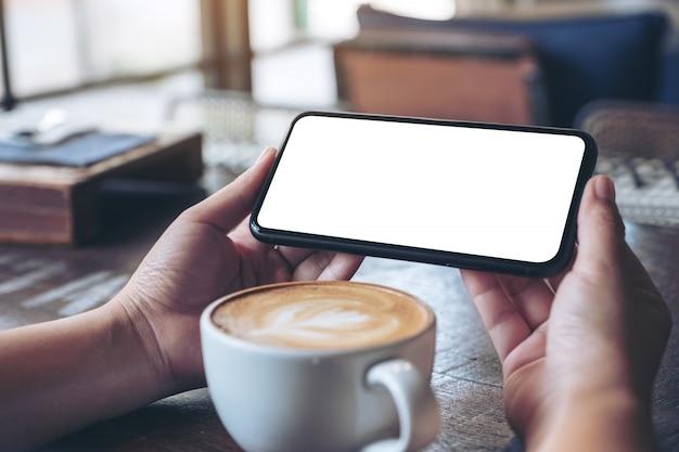 Handen die een zwarte mobiele telefoon met een leeg scherm horizontaal vasthouden en gebruiken om te kijken met een koffiekopje op houten tafel