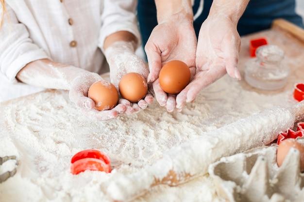 Handen die eieren houden om deeg te maken