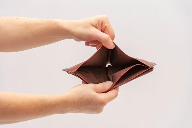 Handen die en open bruine leerportefeuille zonder geld houden tonen