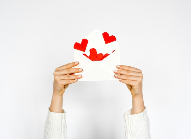 Handen die envelop met harten binnen op witte achtergrond houden