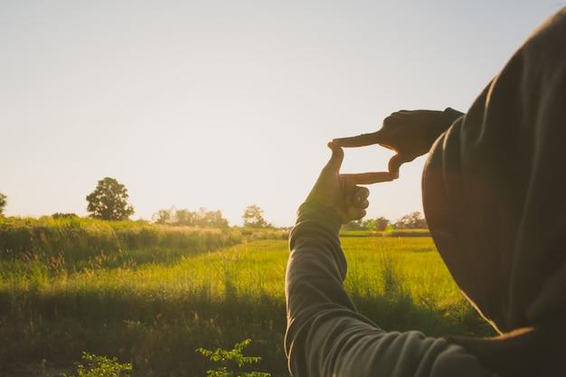 Handen die frame met zonsondergang maken. sluit omhoog van vrouwenhanden makend frame gebaar.