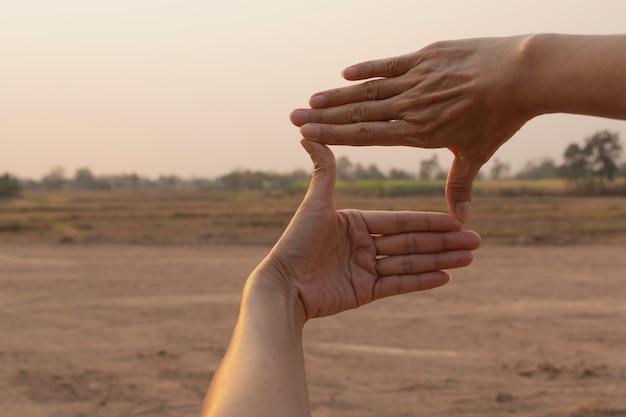 Handen die frame met zonsondergang maken