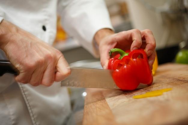Handen die gele peper op professionele keuken snijden