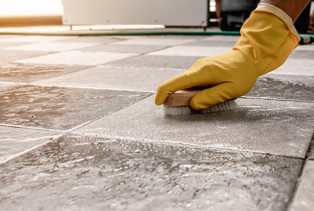 Handen die gele rubberen handschoenen dragen, gebruiken een houten vloerwasser om de tegelvloer te schrobben met een vloerreiniger.