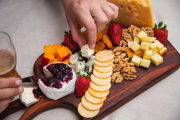Handen die gelei op kaas doorgeven met verschillende kazen op de achtergrondplaat.