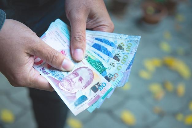 Handen die georgische lari-rekeningen houden. bos van bankbiljetten van het geld van georgië