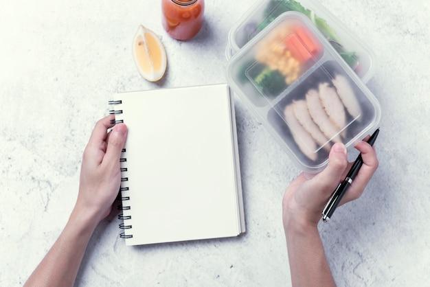 Handen die gezond lunchvakje en leeg notitieboekje voor uw tekstbericht of ontwerp houden, ordevoedsel.