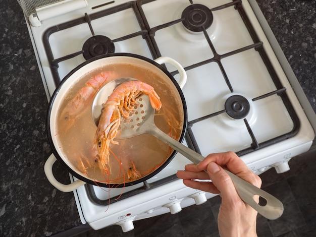 Handen die grote verse garnalen in een kom koken