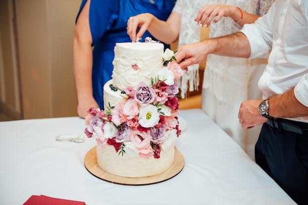 Handen die heerlijke witte huwelijkscake snijden
