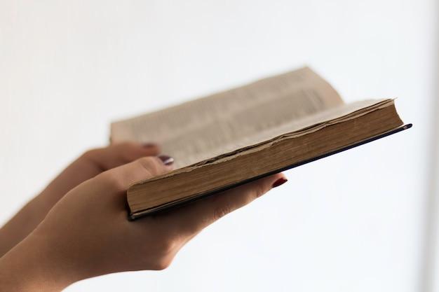Handen die heilige bijbel openhouden en bidden.