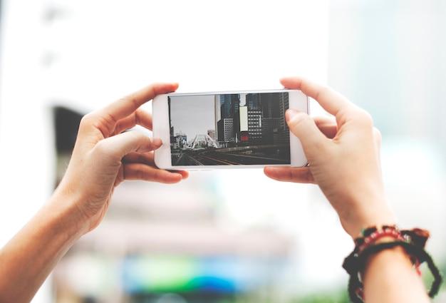Handen die het mobiele telefoonscherm houden die metro de foto van de stadsfoto van het landschap tonen