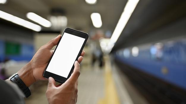 Handen die het smartphone geïsoleerde scherm in metro metro station houden in japan.
