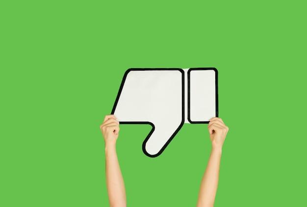 Handen die het teken van afkeer op groene achtergrond houden.