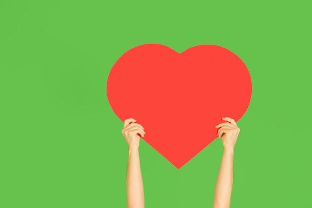 Handen die het teken van hart op groene muur houden.